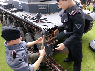 Two 1/6 scale German soldiers fixing a tank tread in a diorama of an army post on display at a scale model exhibition.