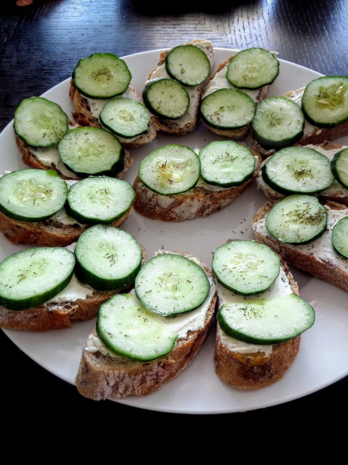 Cucumber Bites:  Crisp, fresh, cucumber slices on baguette spread with cheese.