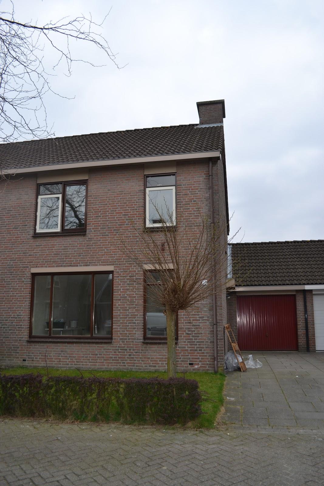 bruine voordeur en wit huis