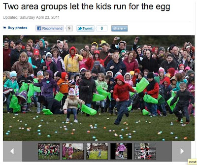 Children running into a field of green grass to grab eggs while a crowd looks on