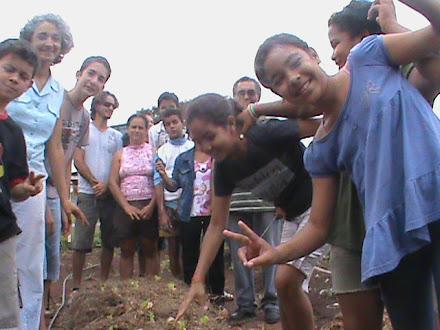 Adriana Galbiati ensinando os alunos a criarem canteiros com o mato retirado da própria horta.