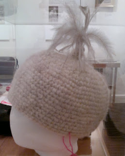 Crocheted beanie-style hat made of raw handspun wool embellished with emu feathers.