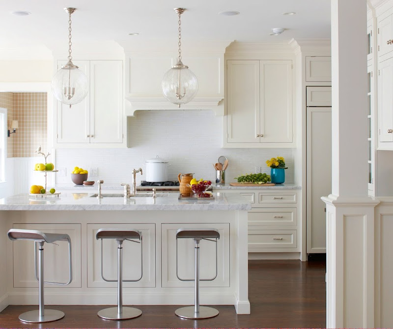 White kitchen with two pendant lights, silver bar stools and a hard wood floor