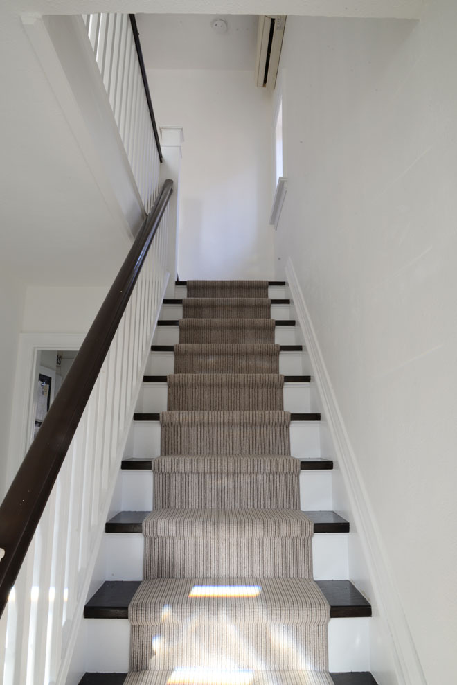 White hallway, striped runner stairs | Benjamin Moore Simply White | Ramblingrenovators.ca