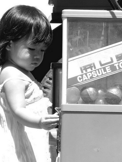 Black and white image of a young girl operating a toy vending / capsule toy machine.