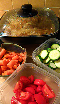 Simmering Meat with Bowls of Carrots, Zucchini, and Tomatoes