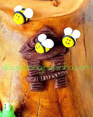 Bolo decorado Smurfs no formato de uma casinha tronco de árvore com abelhinhas na janela da casinha tronco de árvore.