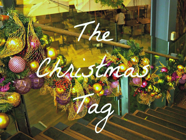 """The Christmas Tag"" text on a festive background of a bauble garland"