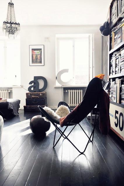 Dekoracje stare walizki, skandynawski design wnętrza, czarna podłoga i krzesło butterfly
