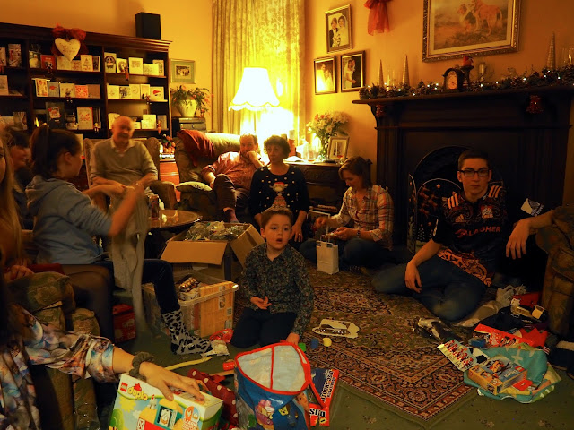 Family unwrapping presents together on Boxing Day