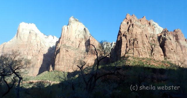 The sun shines on three peaks in the canyon.