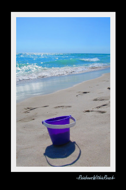 photo of: purple pail on the beach, bucket in the sand, reflection on waves in the ocean