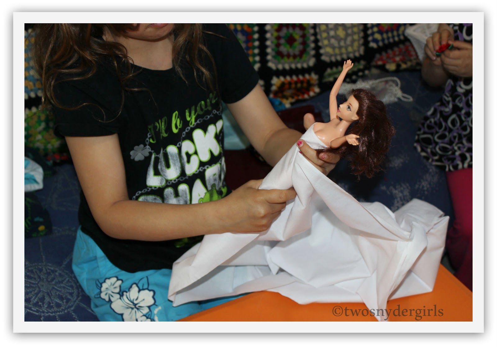 Draping white fabric around a Barbie Doll