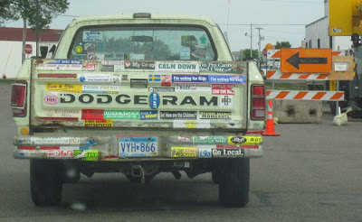 Green Dodge Ram pickup with about two dozen bumper stickers