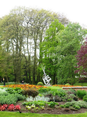 Horn-playing sculpture among flowers in garden