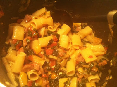 rigatoni being stirred in pot with kale and sausage sauce