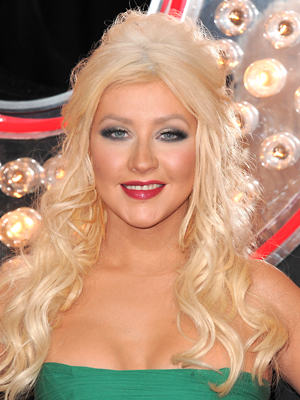 Christina Aguilera goes for a dramatic half-up, half-down hairstyle with a teased top and long waves.