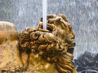 A funnel of water coming out of a bronze-coloured man's head with long hair and beard