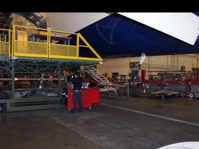 Funcionário realizando reparo em parte de um avião.