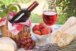 Mesa con comida saludable, pan, frutas y vino.