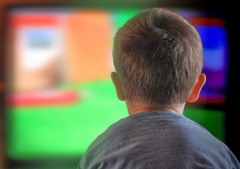 Boy sitting in front of TV