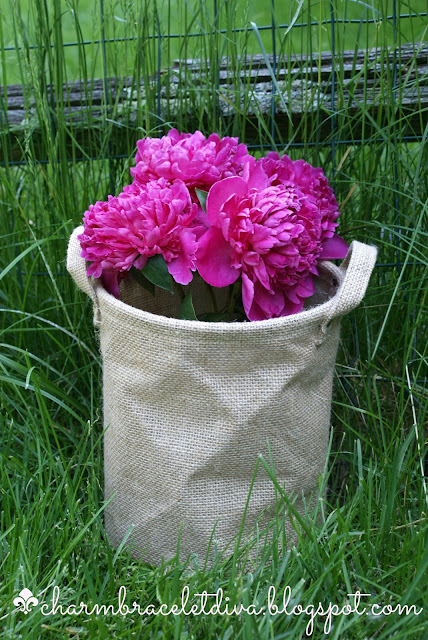 bouquet of pink peonies in a burlap bushel basket