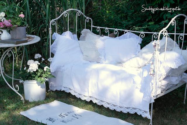 Altes Kinderbett im Garten dekoriert
