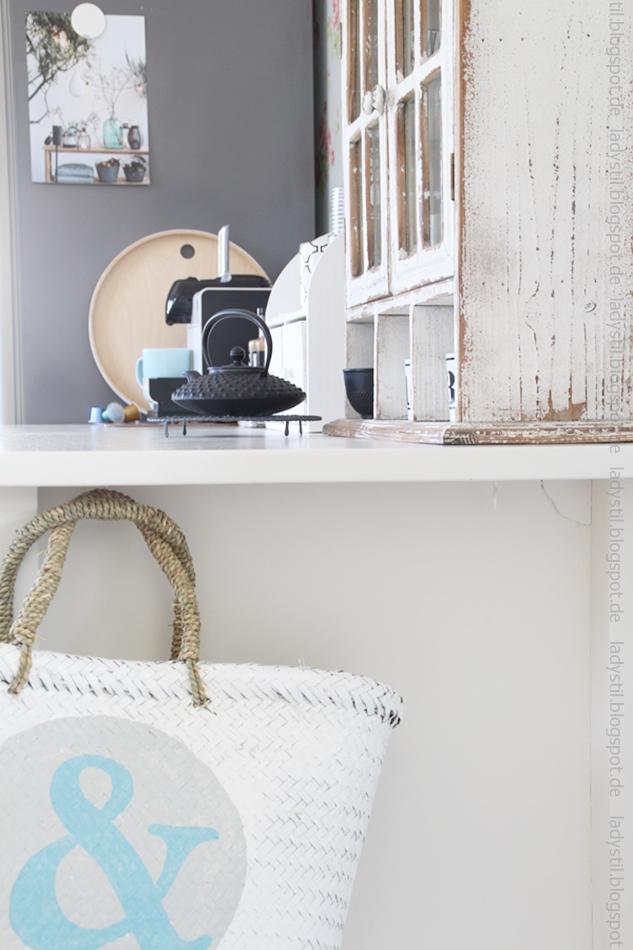 Korbtasche-mit-ampersnad-zeichen-in-hellblau-und-blick-auf-die-Kaffeeecke-in-der-küche