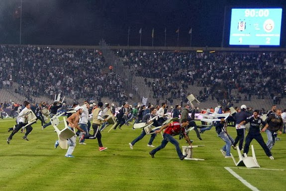 Beşiktaş fans throw chairs and run onto the pitch during a match against Galatasaray