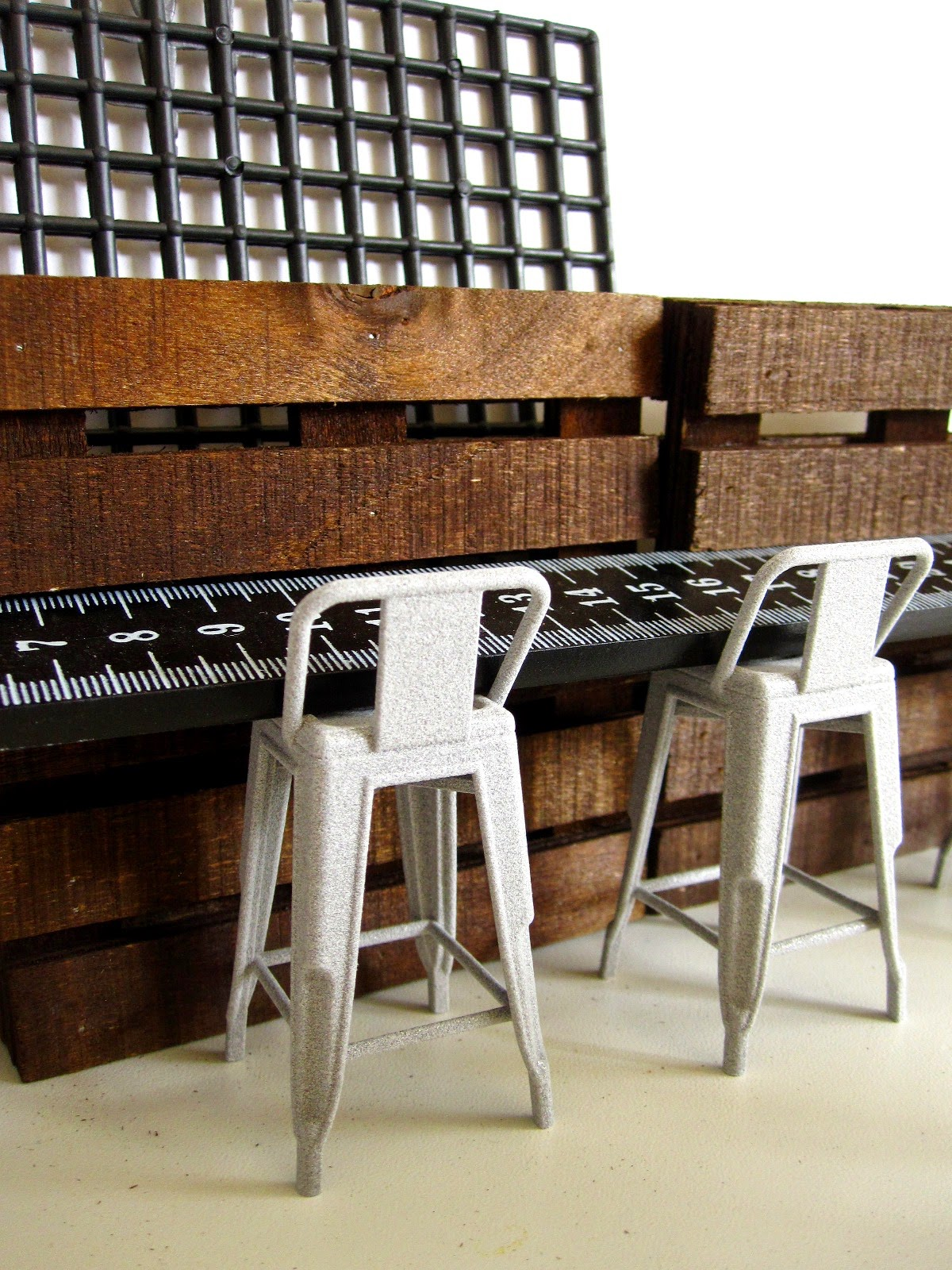 Modern dolls' house miniature cafe stools in front of a counter made from a ruler and miniature pallets.
