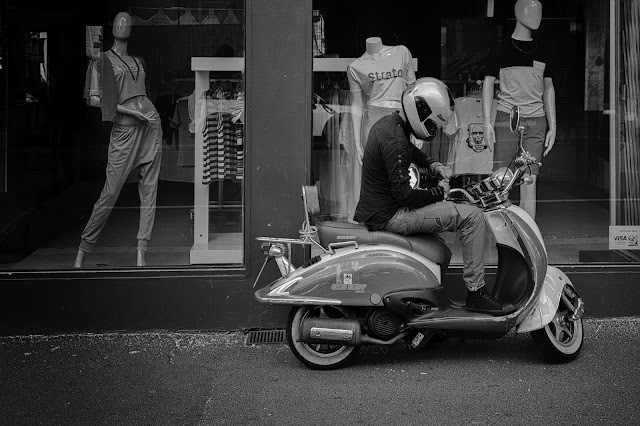 A man gets on a scooter outside a fashion boutique