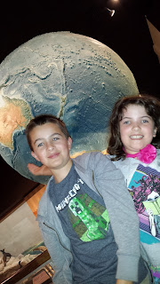 girl and boy in front of a large globe.