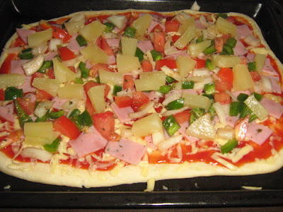 Pizza topped with pineapple, capsicum, ham and tomatoes