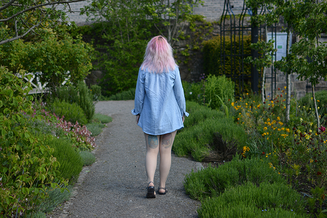 girl walking in garden wearing denim shirt