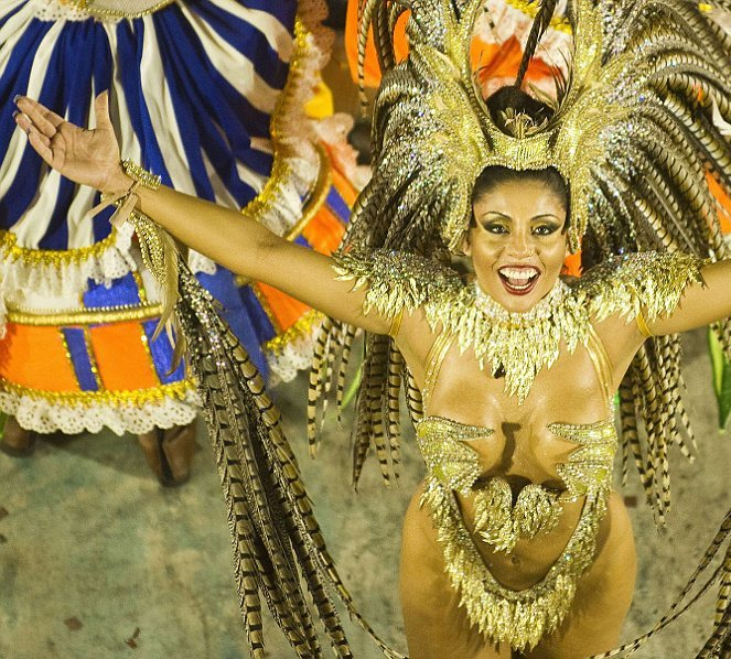 Feathers and glitter: A reveller of Portela samba school performs during the first night of Carnival parade.