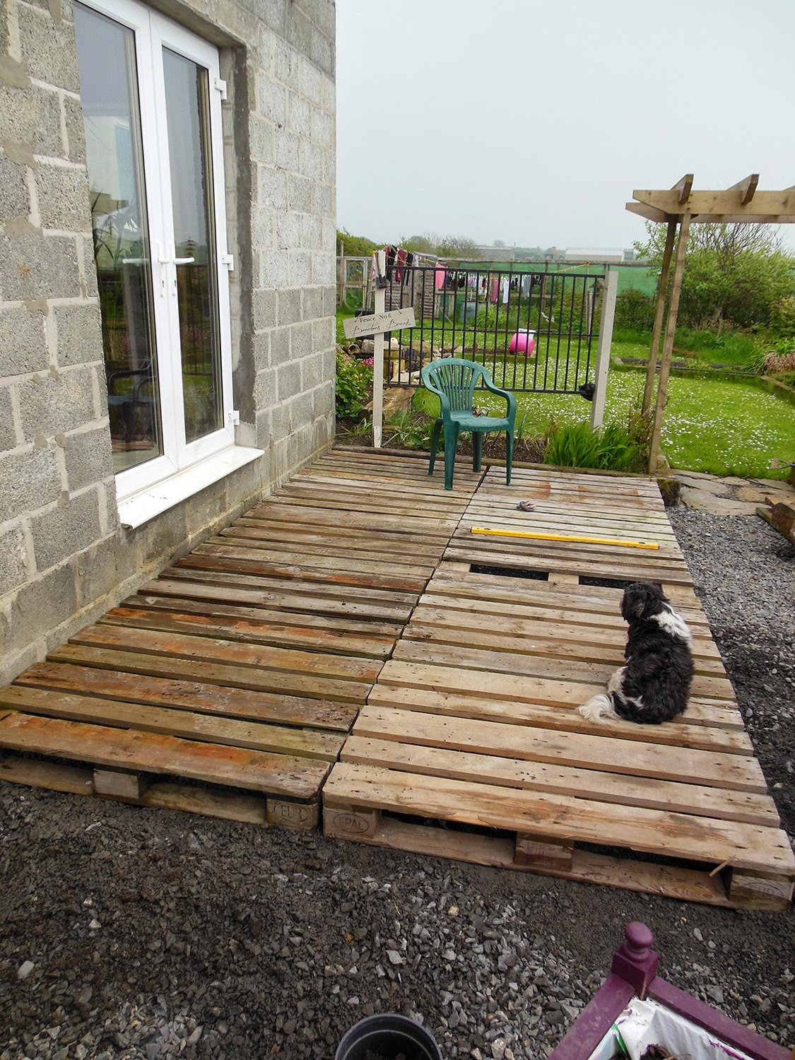 Coach house crafting on a budget diy pallet wood decking for Best material for deck