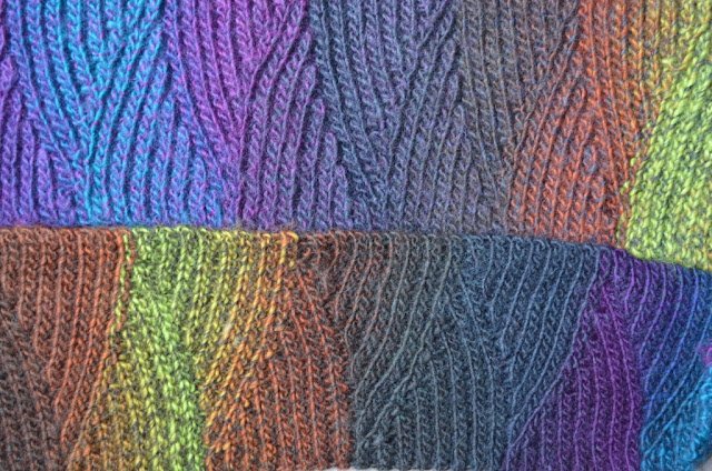 Close up of crocheted scarf made of colour changing yarn: Moda Vera Bouvardia. It blends shades of turquoise, deep blues, purple, grey, charcoal, warm tans and muted lime greens.