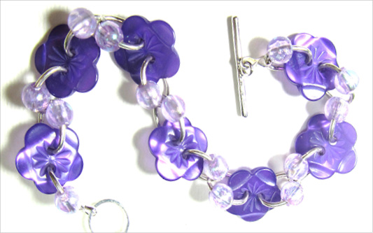 Bracelet has Deep purple flower buttons and lilac accent beads in Half twist design