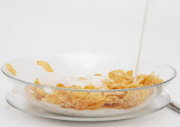 A clear glass bowl with cereal flakes and milk for breakfast.
