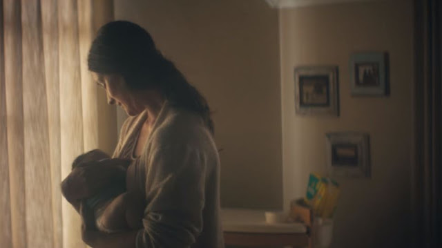 A mother singing a lullaby to a newborn baby to comfort them as part of the Pampers #BetterForBaby Campaign