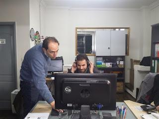Ο Βαγγέλης Αυγουλάς κάθεται σε υπολογιστή και ο υπεύθυνος κ.Γιαννακόπουλος του εξηγεί το παιχνίδι για τα τυφλά παιδιά