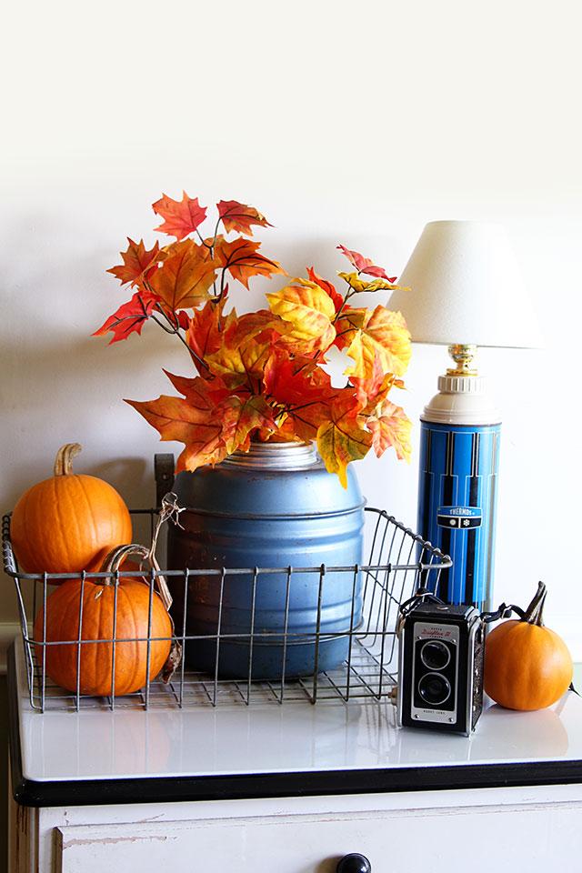 Easy fall vignette with a vintage Thermos jug, dollar store leaf stems and pumpkins.  via houseofhawthornes.com