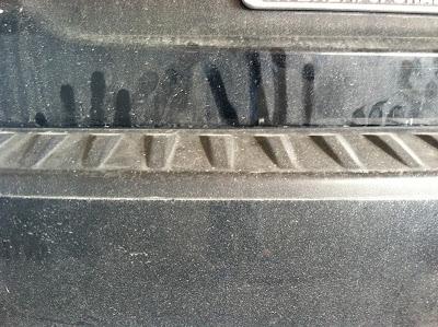 hand print art on a dusty car