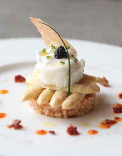 Poached egg on risotto rice cake with white asparagus