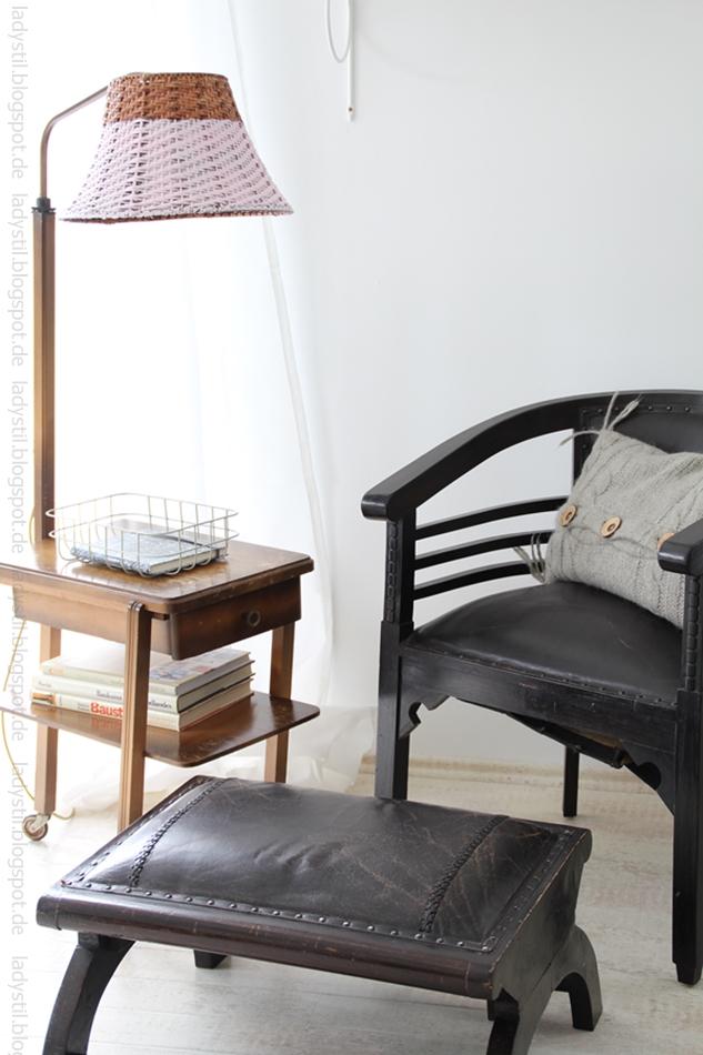 Leseecke mit braunem Holzsessel mit Hocker und einer antiken Stehlampe