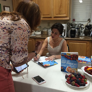 Picture of Amy Riolo signing a cookbook.