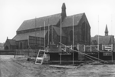 Grayscale photo of a church in the background and a half built structure with scaffolding surrounding it in the foreground.