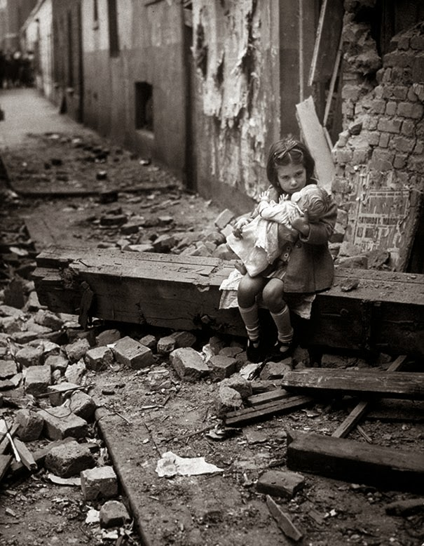 40 Must-See Photos Of The Past - Little girl with her doll sitting in the ruins of her bombed home, London, 1940