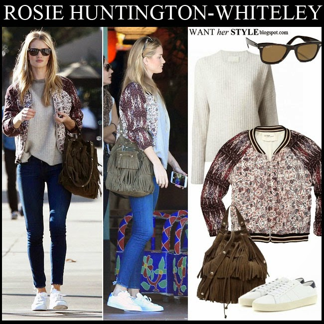 Rosie Huntington-Whiteley in printed bomber jacket, cream knit sweater, blue skinny jeans with fringed bag and white sneakers where to buy want her style november 18