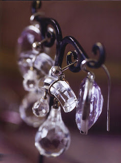 Faceted crystal pendant earrings mode from rock crystal and silver and large shimmering drop earrings made from pale amethyst. They are shown hanging from an antique bronze holder.